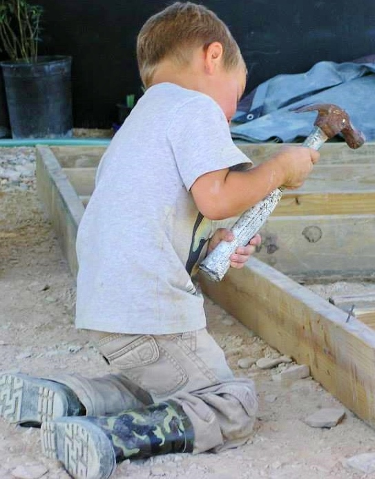 A young kiddo helps build at the community garden.